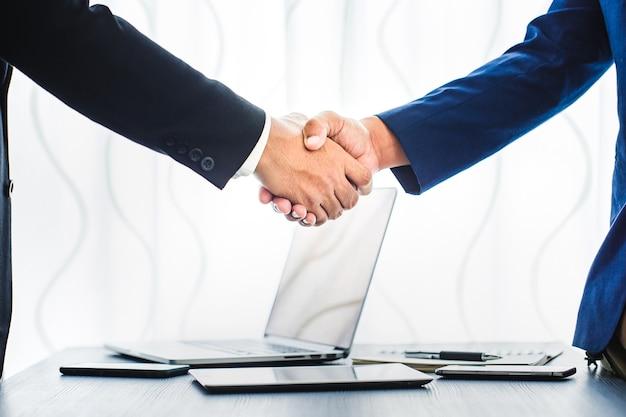 Conceito do negócio, aperto de mão do homem de negócios no espaço de trabalho do escritório para o investimento