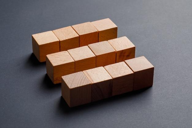 Conceito do negócio com os cubos de madeira na opinião de ângulo alto da tabela cinzenta escura.
