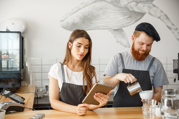 Conceito do negócio do café - baristas alegres que olham seus comprimidos para pedidos on-line no café moderno.