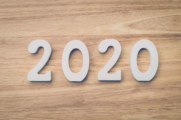 Conceito do negócio e de projeto - número de madeira 2020 para o texto do ano novo feliz na tabela de madeira.