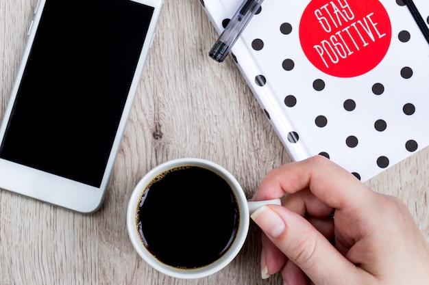 Conceito do negócio e do escritório - caderno preto, branco da tampa do às bolinhas, smartphone e copo do café preto na tabela de madeira. vista do topo.
