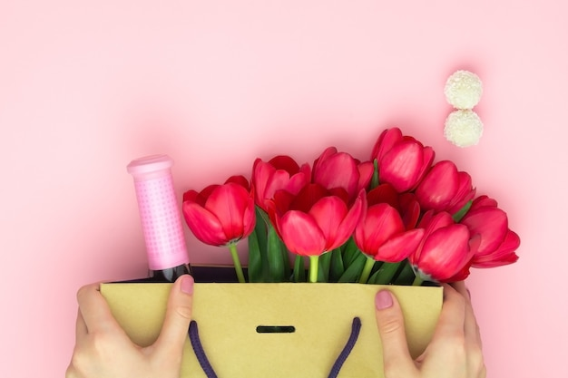 Conceito do presente com vinho e tulipas vermelhas no saco de papel no fundo rosa. postura plana, cópia espaço. mãos de mulher segurar um presente para o dia das mulheres, dia das mães, conceito de primavera. decoração de flores