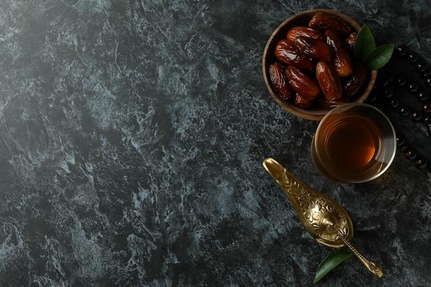 Conceito do ramadã com comida e acessórios em uma superfície preta esfumada