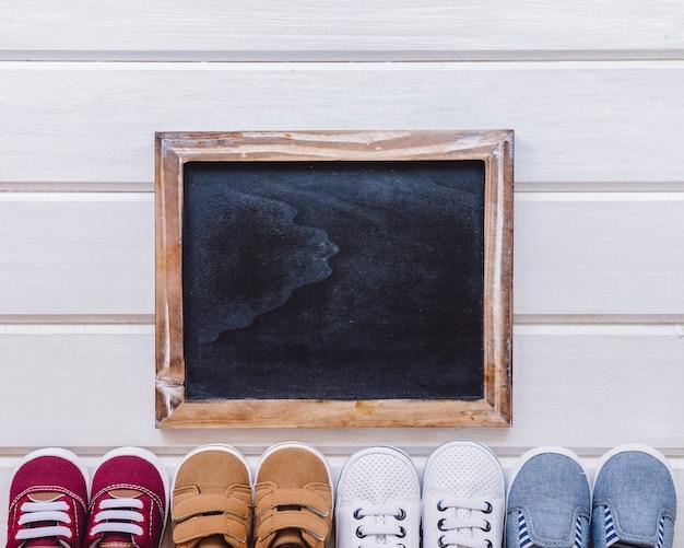 Conceito do recém nascido com ardósia e sapatos
