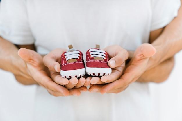 Conceito do recém nascido com o casal gay segurando sapatos