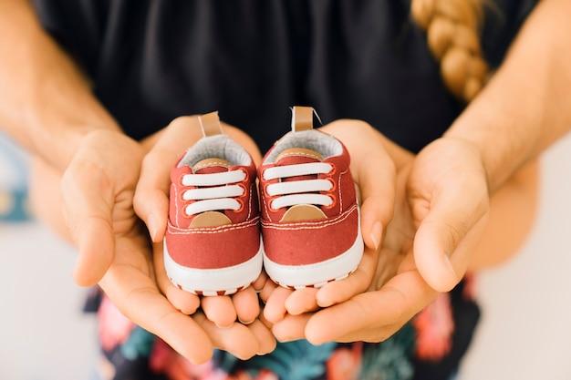 Conceito do recém nascido com o casal segurando sapatos nas mãos