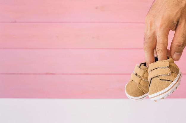 Conceito do recém nascido com os dedos segurando sapatos