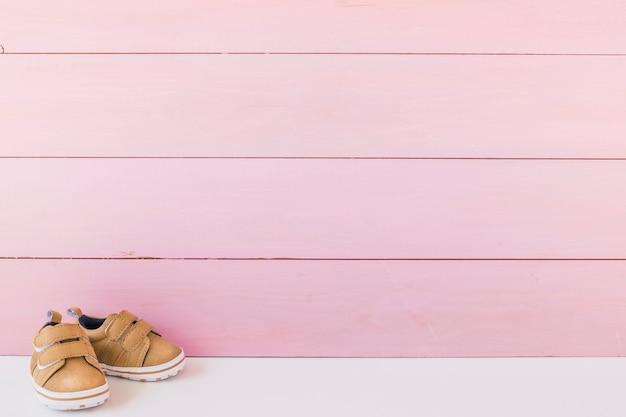 Conceito do recém nascido com sapatos e espaço na superfície de madeira