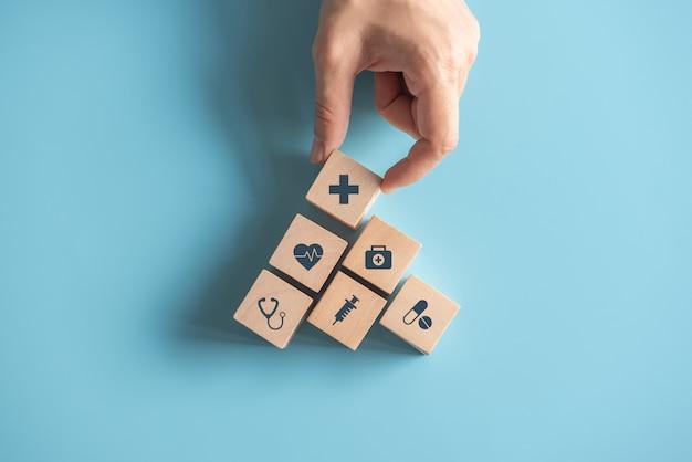 Conceito do seguro de saúde, mão da mulher que arranja o cubo de madeira que empilha com os cuidados médicos do ícone médicos na parede azul, espaço da cópia.