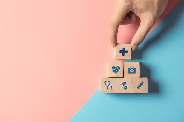 Conceito do seguro de saúde, mão do homem que arranja o cubo de madeira que empilha com os cuidados médicos do ícone médicos no fundo azul e cor-de-rosa pastel, copia o espaço.