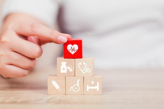 Conceito do seguro de saúde, mão que arranja o bloco de madeira que empilha com os cuidados médicos do ícone médicos.
