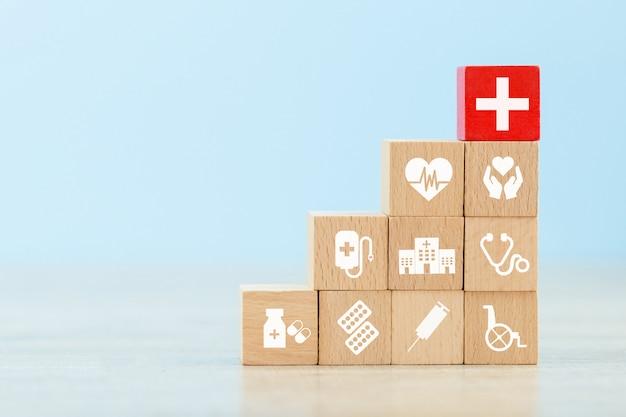Conceito do seguro de saúde, organizando o bloco de madeira que empilha com os cuidados de saúde do ícone médicos.