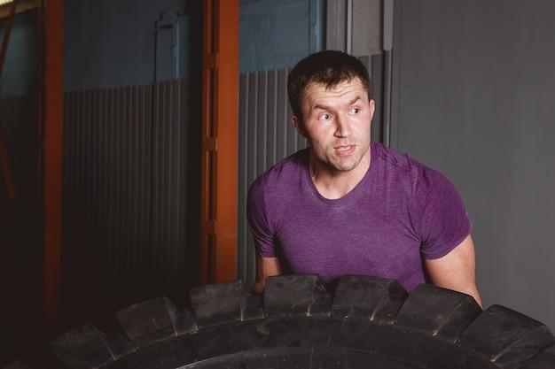Conceito do treinamento do esporte de crossfit - homem que lança o pneu.