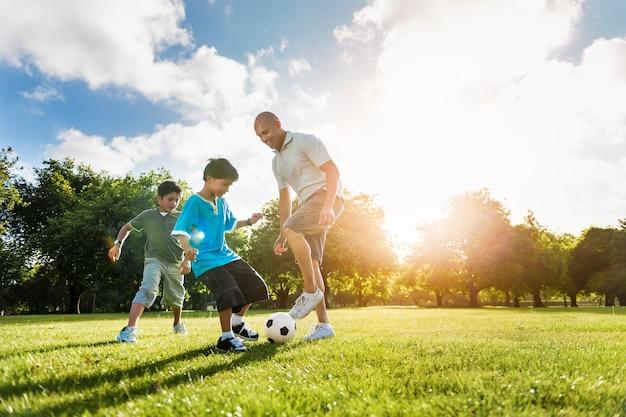 Conceito do verão da atividade do filho do pai do campo de futebol do futebol