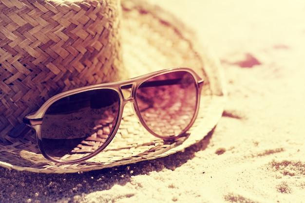 Conceito do verão ou das férias. óculos de sol bonitos com chapéu de palha na areia. de praia. estilo de vida. tonificação.