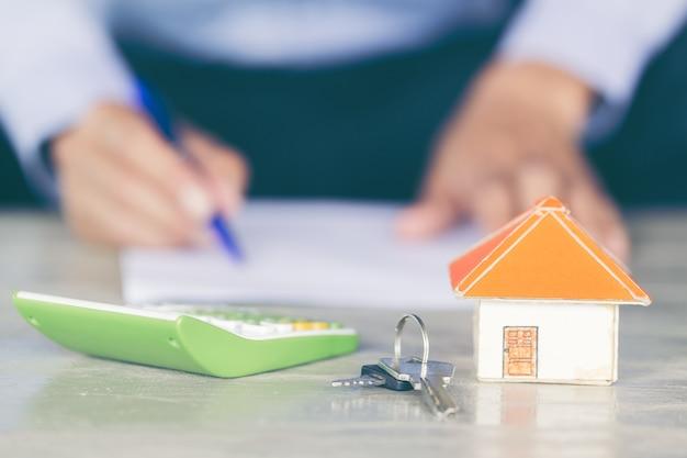 Conceito dos bens imobiliários - o homem de negócio assina o contrato atrás do modelo arquitectónico da casa.
