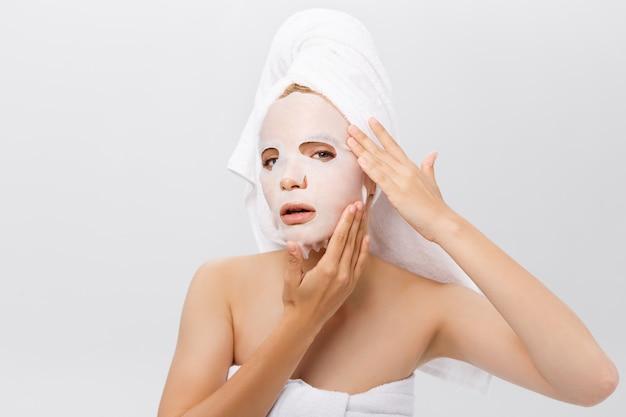 Conceito dos cuidados com a pele da beleza - mulher caucasiano bonita que aplica a máscara de papel da folha em seu fundo do branco da cara.