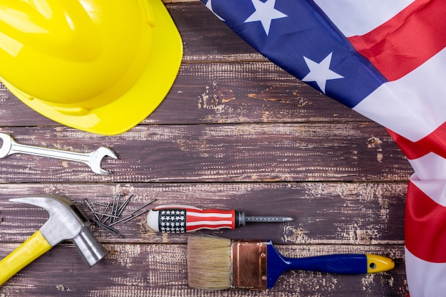 Conceito dos eua do dia do trabalhador, grupo de várias ferramentas, bandeira dos eua no fundo de madeira com espaço da cópia para o texto.