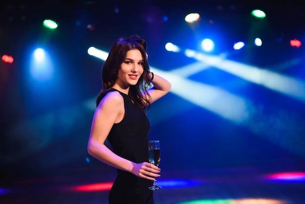 Conceito dos feriados, da vida noturno, das bebidas, dos povos e do luxo - champanhe bebendo da jovem mulher bonita no partido sobre o fundo das luzes.