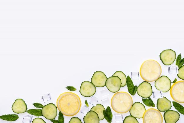 Conceito dos ingredientes da limonada ou do mohito no branco. fatias de limão, folhas de hortelã, pepino e cubos de gelo.