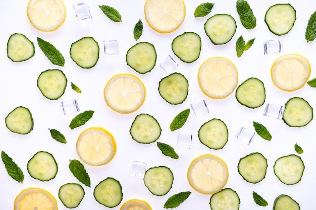 Conceito dos ingredientes da limonada ou do mohito no branco. rodelas de limão, folhas de hortelã, pepino e cubos de gelo.