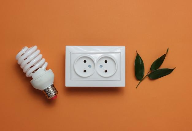 Conceito ecológico energia energia economia salve o planeta tomada de energia dupla verde com lâmpada espiral em fundo marrom