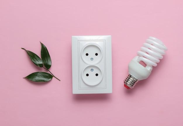Conceito ecológico energia energia economia salve o planeta tomada dupla de energia verde com lâmpada espiral em fundo rosa pastel
