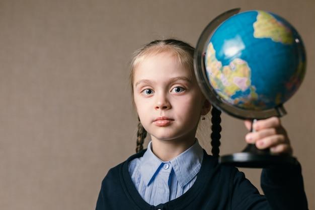 Conceito - educação. menina caucasiana, segurando um globo
