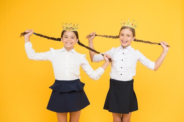 Conceito egoísta. rainha do baile. orgulho da infância. sucesso na educação. de volta à escola. meninas egoístas sonham com o futuro. garotas felizes de uniforme e coroa. grande chefe. motivação para estudar. moda infantil.