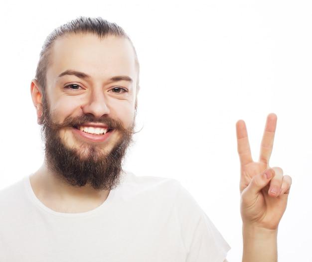 Conceito emocional e as pessoas: jovem barbudo com sinal de boa ideia. estilo moderno.