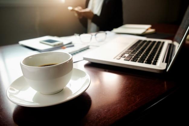 Conceito empresarial com espaço de cópia. mesa de escritório com foco na caneta e quadro de análise, computador, caderno, xícara de café na mesa. tons de entrada. filtro retro, foco seletivo.