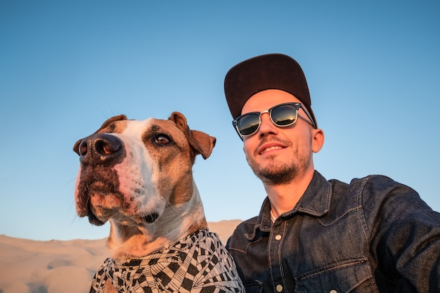 Conceito engraçado de melhores amigos: humano tomando uma selfie com cachorro. jovem do sexo masculino fazendo um autorretrato mimado com seu cachorro ao ar livre