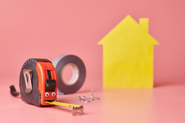 Conceito engraçado de renovação de casa. fita métrica de metal e outros itens de reparo. reparo em casa e conceito redecorado. casa amarela em forma de figura em fundo rosa.