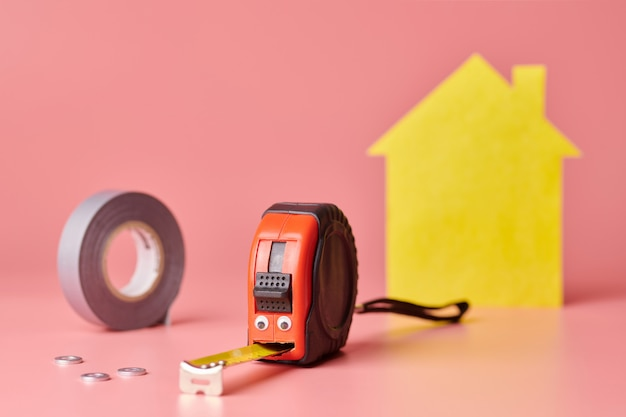 Conceito engraçado de renovação de casa. fita métrica de metal e outros itens de reparo. reparo em casa e conceito redecorado. casa amarela