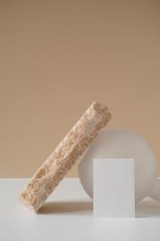 Conceito estético mínimo criativo com cartão de folha de papel em branco, pedra de mármore rosa, vaso branco contra parede bege neutra.
