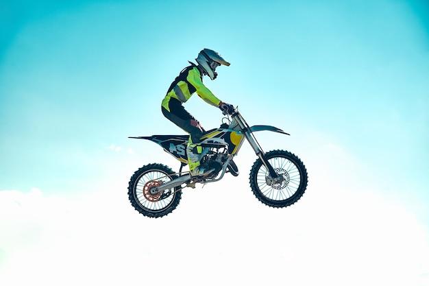 Conceito extremo, desafie-se. salto extremo em uma motocicleta em um fundo de céu azul com nuvens. copie o espaço, tudo ou nada.