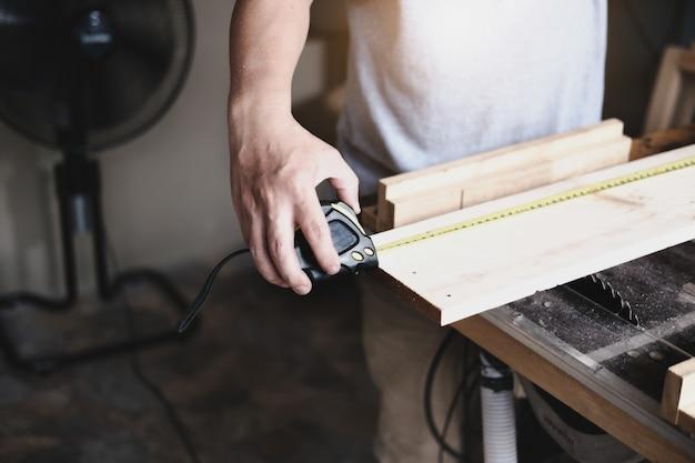 Conceito faça você mesmo os artesãos usam uma fita métrica para montar peças de madeira para fazer mesas de madeira para os clientes.