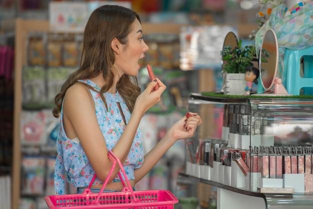 Conceito feliz do tempo da compra, mulher asiática com batom da compra da cesta na loja da beleza.