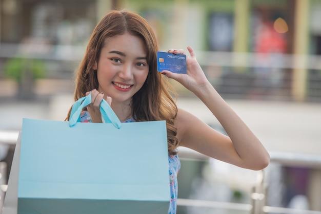 Conceito feliz do tempo da compra, mulher asiática nova com sacos de compras e cartão de crédito guardando à disposição na alameda.