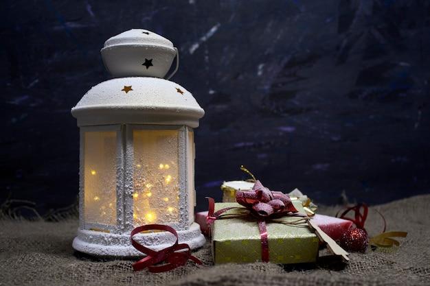 Conceito festivo de natal e ano novo. uma bela lâmpada decorativa brilha em um espaço escuro com caixas de presente, tambores e uma árvore de natal de madeira.