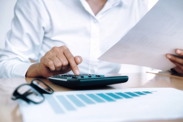 Conceito finanças economia econômica. contabilista feminino ou calculadora de uso de banqueiro.