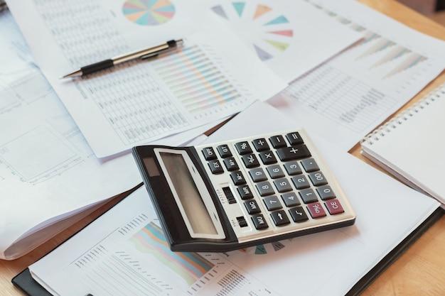 Conceito financeiro de negócios com calculadora caneta notbook e relatório contábil na mesa