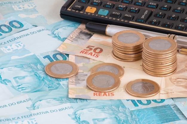 Conceito financeiro notas e moedas de cem reais com calculadora e caneta dinheiro brasileiro