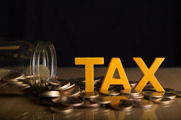 Conceito fiscal. o imposto da palavra pôs sobre moedas e garrafas de vidro com moedas para dentro no fundo preto.
