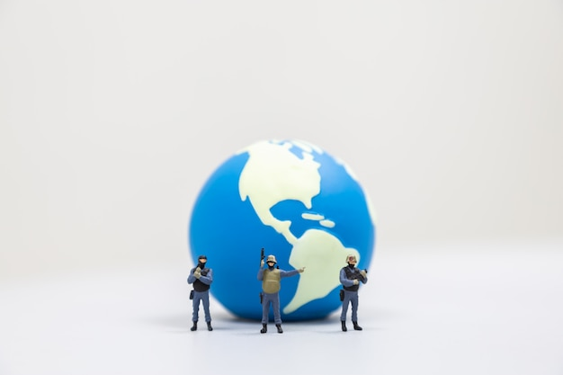 Conceito global de defesa e proteção. feche acima do grupo de soldado diminuto dentro com a arma que está na frente da mini bola do mundo no branco.