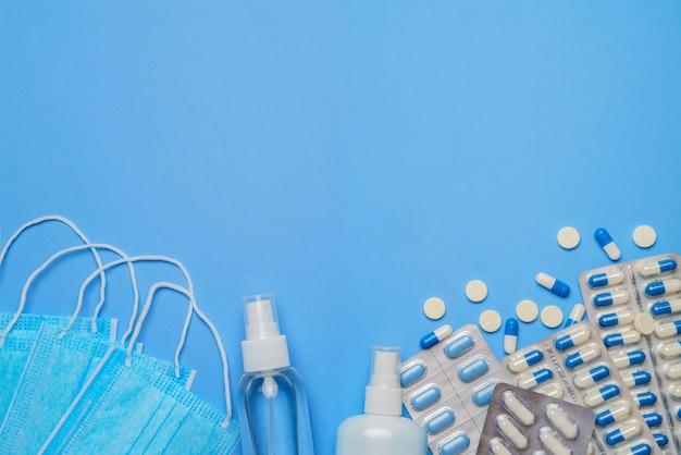 Conceito global de proteção contra pandemia de coronavírus - máscaras cirúrgicas médicas, gel desinfetante para as mãos e castração para higiene e pílulas