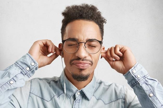 Conceito humano, lazer e tecnologia moderna. foto interna de um homem bonito de pele escura com cabelo encaracolado,