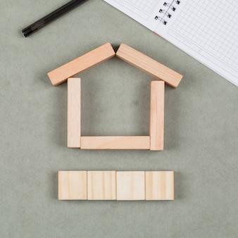 Conceito imobiliário com blocos de madeira, caderno, caneta em close-up de fundo cinza.
