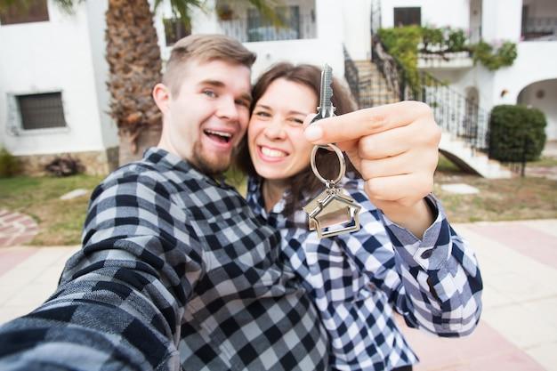 Conceito imobiliário e de propriedade - casal feliz segurando as chaves da nova casa e da miniatura da casa