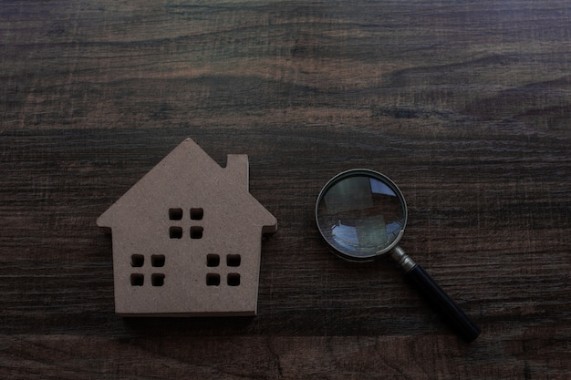Conceito imobiliário e inspetor, modelo de casa e lupa na mesa de madeira